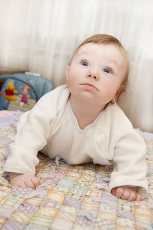 curiously: Cute baby boy lying on bed and looking curiously up