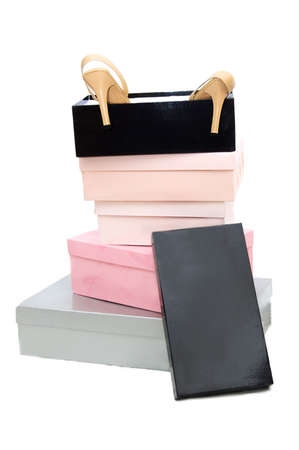 Pile of boxes and woman high-heeled shoes over white photo
