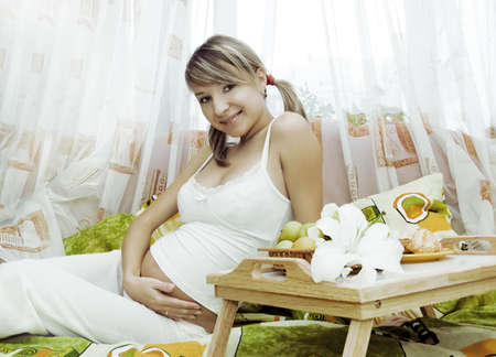 Pretty pregnant woman having breakfast in bed Stock Photo - 6054518
