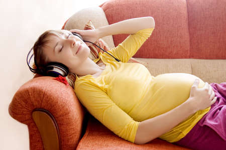 music therapy: Pregnant woman with headphones lying on sofa