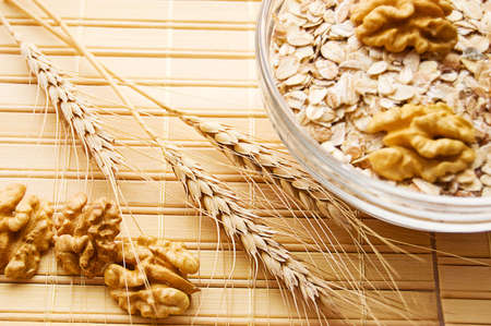 Bowl full of oatmeal with dry wheat and nuts, focus on wheat Stock Photo