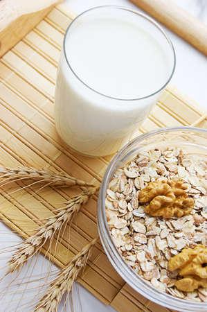 Morning porridge, nuts, wheats and glass of milk photo