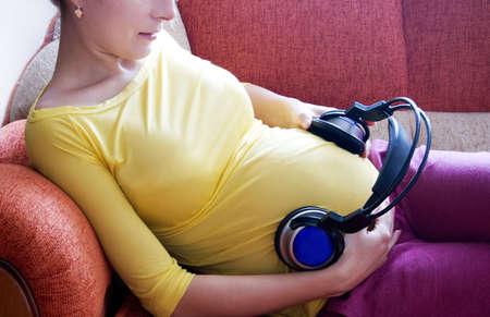 musicoterapia: Donna incinta con cuffie sulla sua pancia sdraiata sul divano