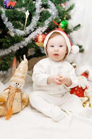 Baby in santa hat sitting under Christmas tree Stock Photo - 6192027