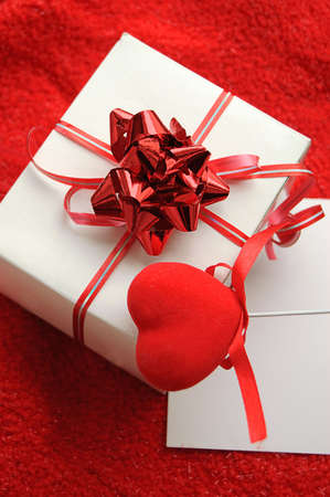 Gift box and fabric heart over red background photo