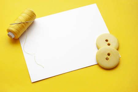 kit de costura: Subproceso amarillo, agujas y algunos botones de nota en blanco