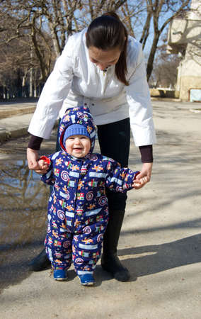 Baby walks in the park holding mother hands photo