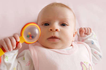 Three months old baby girl holding rattle Stock Photo - 6998585