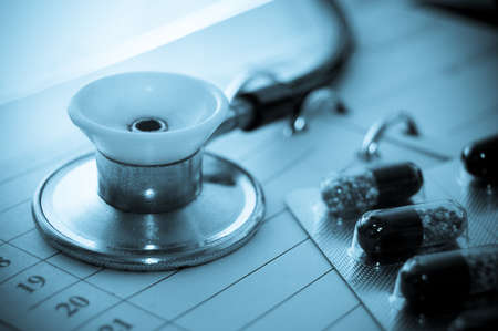 Stethoscope and pills on notebook