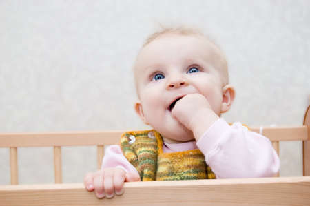 Curious baby with finger in mouth standing in bed photo