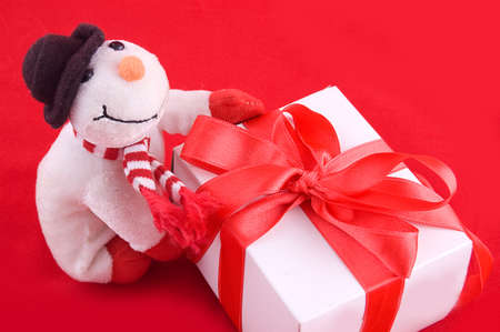 Snowman and giftbox on red background photo