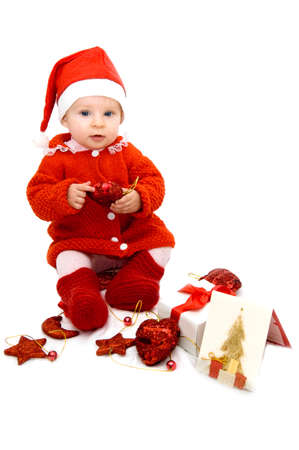 Baby as Santa helper sitting with Christmas decoration photo