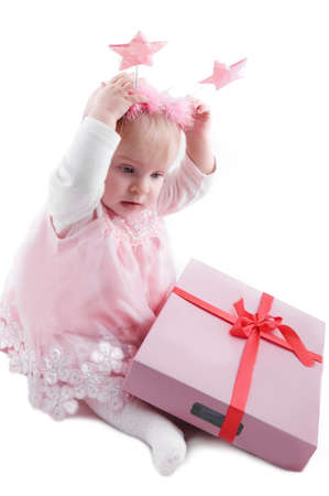 Baby girl in pink dress with gift box over white photo