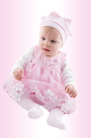 Baby girl in fancy dress over pink background photo
