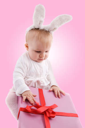 Baby in rabbit costume with pink gift photo