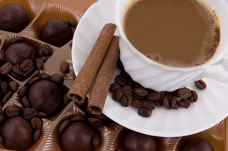 Cup of cappuccino, chocolate pralines, cinnamon sticks and beans photo