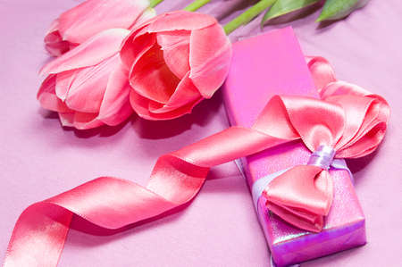 Tulips and gift box with ribbon on pink photo