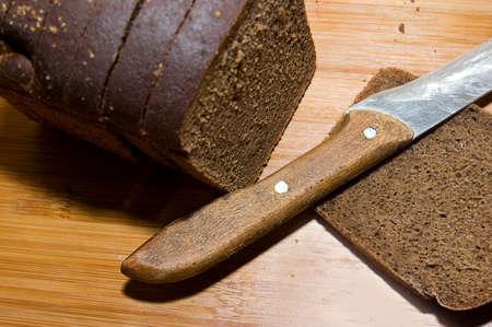 Hogaza de pan negro y cuchillo sobre plancha de madera Foto de archivo - 8997249