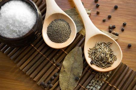 Salt, pepper, zira and bay leaf on wooden plate Stock Photo - 9071233