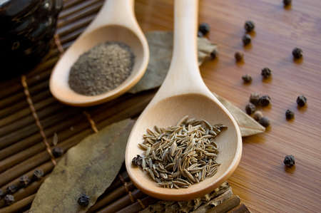 Cumin on wooden spoon with bay leaf and pepper Stock Photo - 9130875