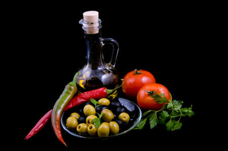 tableware life: Olive oil, tomatoes, pepper and greens isolated on black