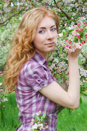 Sensual red-haired woman among apple blossom Stock Photo - 9505065