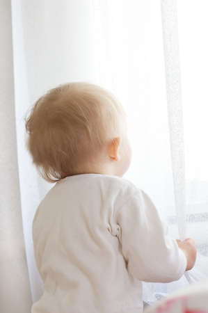 quiet baby: Little baby girl with its back looking in window through curtains