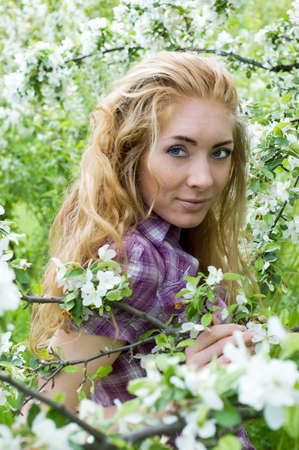 redheaded: Red-headed woman in cherry tree blossom Stock Photo