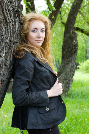 Redheaded woman standing under tree photo