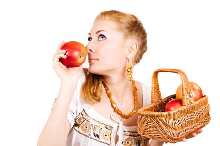 Redheaded woman smelling red apple over white photo
