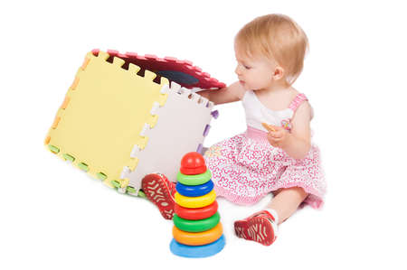 Baby girl playing pyramide and cube over white photo