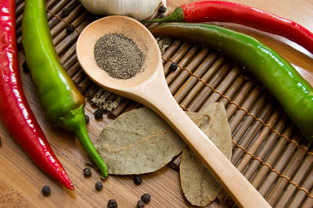 Some kinds of pepper and bay leaf on wooden plate photo