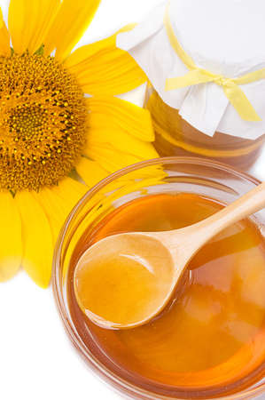 Honey in jar with wooden spoon and sunflower