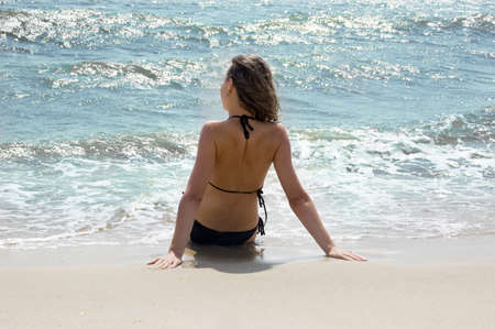Woman in black bikini sitting with her back at sea shore photo