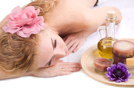 Redheaded woman lying with spa products over white Stock Photo - 10590126