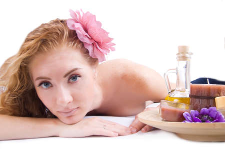 Redheaded woman lying with spa products over white Stock Photo - 10590122