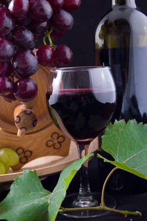 Red wine bottle, glass and cask with grapes over black Stock Photo - 10723318