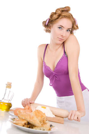 Lovely housewife with rollers baking over white photo