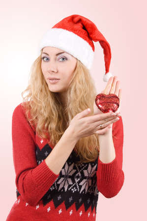 Woman in Santa hat holding red heart over light red back Stock Photo - 11807496