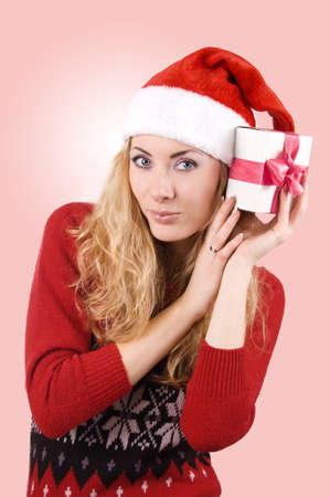 Pretty woman in Santa hat holding present over light red back Stock Photo - 11807494