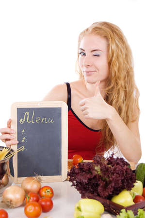 Woman winks with menu board, vegetables and thumb up over white Stock Photo - 11929690