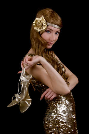 Retro-styled woman in golden dress and shoes over black photo