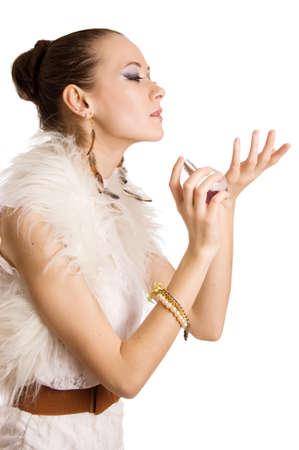 Fashion woman applying perfume on her waist over white photo