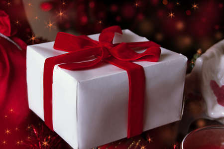 Gift with red ribbon and Christmas tree photo