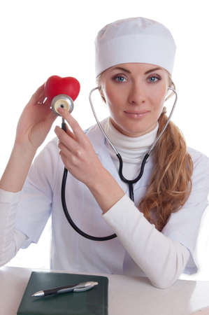 Female docotr examining red heart with stethoscope isolated on white Stock Photo - 12170400