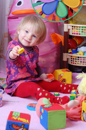 Baby girl in nursery playing toys