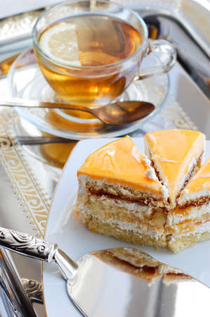 Piece of cake with apricot and tea on tray photo