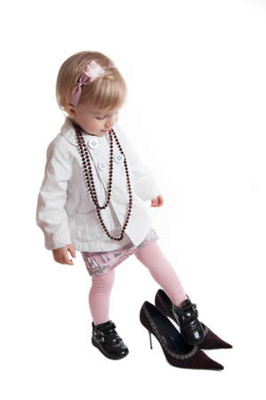 Little girl wearing mothers shoes and jewelry over white photo