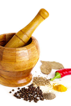 Mortar with pestle and variety of spices over white photo