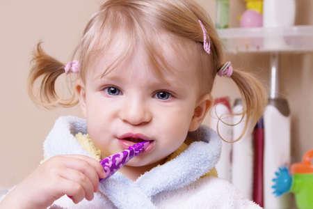 Little girl brushing her teeth in bath photo